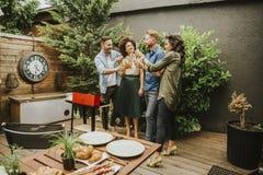 Amis grillant la nourriture et appréciant la partie de barbecue Photographie stock