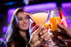 Amis grillant le cocktail au compteur de barre Images stock