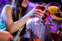 Amis grillant le cocktail au compteur de barre Photographie stock libre de droits