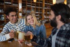 Amis grillant le verre de boissons dans la barre Images stock