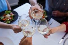 Amis grillant le verre de vin tout en prenant le déjeuner Image libre de droits