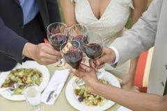 Amis grillant le vin au Tableau de Dinning Image stock