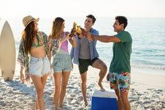 Amis grillant sur le rivage à la plage Photo stock
