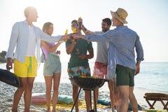Amis grillant tout en se tenant prêt le barbecue à la plage Photos libres de droits