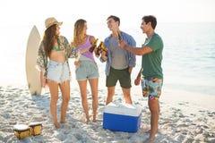 Amis grillant tout en se tenant sur le rivage à la plage Image stock