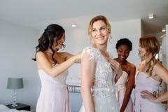 Amis habillant la jeune mariée pour épouser Photos stock