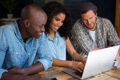 Amis heureux à l'aide de l'ordinateur portable dans le café Image stock