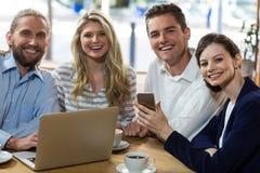 Amis heureux à l'aide de l'ordinateur portable et du téléphone portable Photographie stock