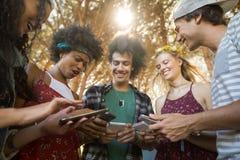 Amis heureux à l'aide des téléphones portables ensemble au terrain de camping Photos stock