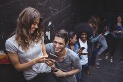 Amis heureux à l'aide des téléphones portables tout en se tenant prêt le mur Photo libre de droits