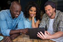 Amis heureux à l'aide du comprimé numérique dans le café Images stock