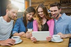 Amis heureux à l'aide du comprimé numérique tout en ayant le café Images stock