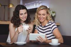 Amis heureux à l'aide du comprimé numérique tout en ayant le café Image stock