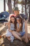 Amis heureux à l'aide du téléphone intelligent tout en se reposant sur le champ Photographie stock libre de droits