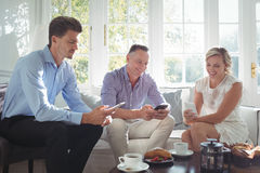 Amis heureux à l'aide du téléphone portable tout en prenant le petit déjeuner Photo libre de droits