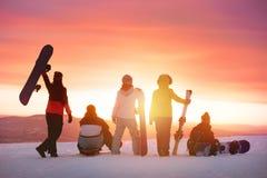 Amis heureux à la station de sports d'hiver contre le coucher du soleil Photographie stock