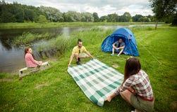 Amis heureux étendant la couverture de pique-nique au terrain de camping Photographie stock