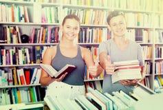 Amis heureux achetant de nouveaux livres et montrant des pouces  Photographie stock
