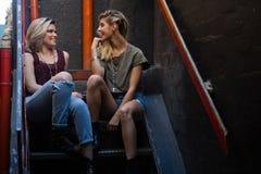 Amis heureux agissant l'un sur l'autre les uns avec les autres sur l'escalier Image stock