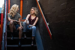 Amis heureux agissant l'un sur l'autre les uns avec les autres sur l'escalier Photos libres de droits