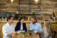 Amis heureux agissant l'un sur l'autre les uns avec les autres tout en ayant le café Images stock