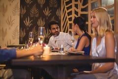 Amis heureux agissant l'un sur l'autre les uns avec les autres tout en ayant le champagne Image stock