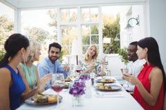 Amis heureux agissant l'un sur l'autre les uns avec les autres tout en ayant le repas Image libre de droits