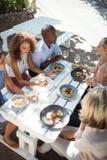 Amis heureux agissant l'un sur l'autre les uns avec les autres tout en ayant le repas Photographie stock libre de droits
