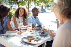 Amis heureux agissant l'un sur l'autre les uns avec les autres tout en ayant le repas Photographie stock