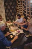 Amis heureux agissant l'un sur l'autre les uns avec les autres tout en dînant Images stock