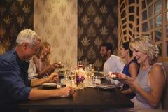 Amis heureux agissant l'un sur l'autre les uns avec les autres tout en dînant Image stock