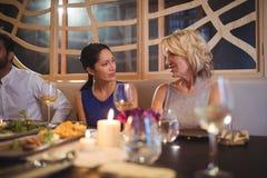 Amis heureux agissant l'un sur l'autre les uns avec les autres tout en dînant Photo stock