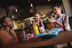 Amis heureux agissant l'un sur l'autre tout en ayant le repas et la bière Image stock
