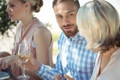 Amis heureux agissant l'un sur l'autre tout en ayant le verre de vin Images stock