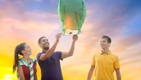 Amis heureux allumant la lanterne chinoise de ciel Photo libre de droits