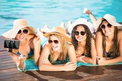 Amis heureux appréciant à la piscine Image stock