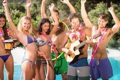 Amis heureux appréciant à la piscine Image libre de droits
