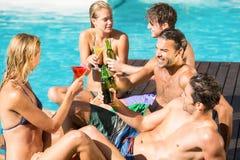 Amis heureux appréciant à la piscine Photos libres de droits