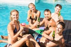 Amis heureux appréciant à la piscine Photo stock