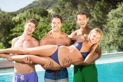 Amis heureux appréciant à la piscine Photographie stock libre de droits