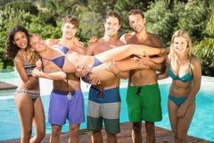 Amis heureux appréciant à la piscine Photo libre de droits