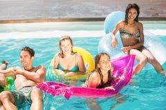 Amis heureux appréciant dans la piscine Images stock