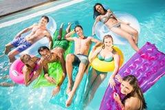 Amis heureux appréciant dans la piscine Photographie stock