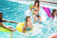 Amis heureux appréciant dans la piscine Images libres de droits