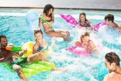 Amis heureux appréciant dans la piscine Photographie stock libre de droits