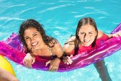 Amis heureux appréciant dans la piscine Photos stock