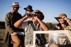 Amis heureux appréciant dans le véhicule pendant des vacances de safari Image libre de droits