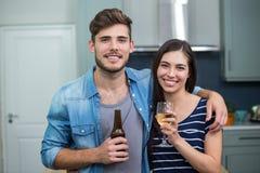 Amis heureux appréciant des boissons à la maison Photographie stock