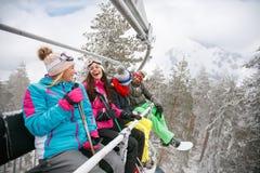 Amis heureux appréciant en quelques vacances d'hiver Ils montent vers le haut du lif de ski Photo libre de droits