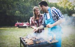 Amis heureux appréciant la partie de barbecue Photo stock